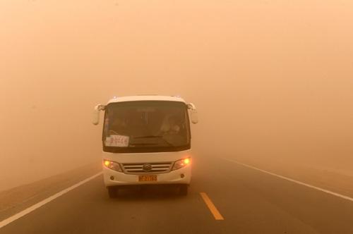 """7月20日,在柳格高速甜水井服务区附近的公路上,一辆客运班车因强沙尘天气紧急停车。当日,甘肃河西走廊西端的酒泉市敦煌、瓜州一带出现夏季罕见的强沙尘天气,连接敦煌至瓜州的柳格高速部分路段甚至完全无法看清前方道路,有的车辆在路边临时停车,有的车辆打着""""双闪""""缓慢行驶。据了解,酒泉市气象台7月20日9时22分发布大风蓝色预警信号,预计未来24小时,酒泉市将出现5至6级大风,部分地方伴有沙尘。"""