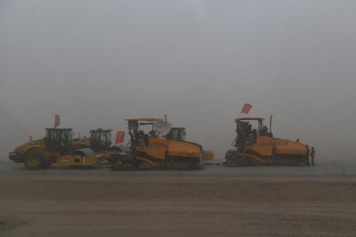 7月20日,在柳格高速旁的施工道路上,施工人员因沙尘天气停止施工。