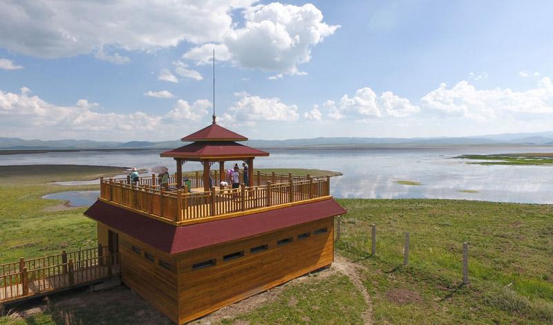 7月18日,游客在甘肃省甘南藏族自治州碌曲县尕海湖边的观景台上游览。