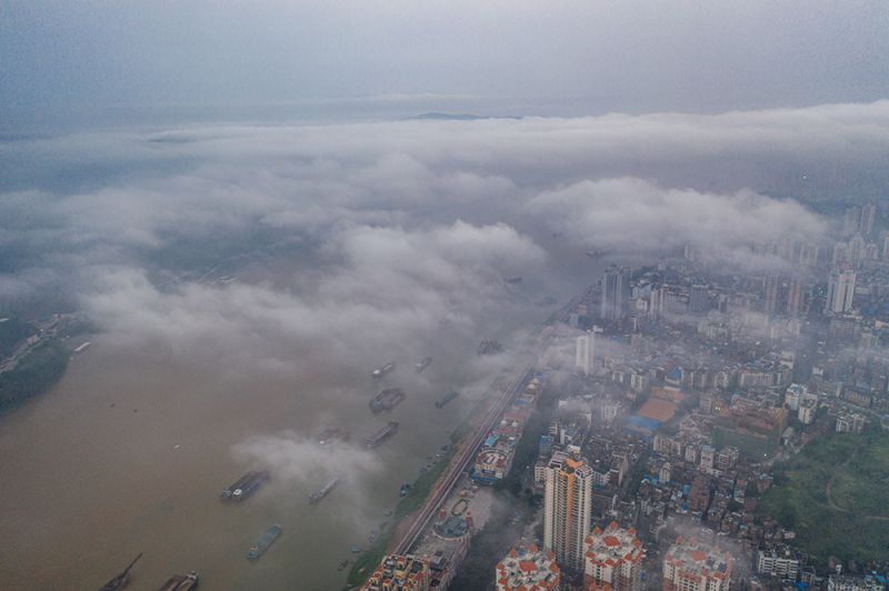 5、江河船只和城市建筑在云雾中若隐若现(何华文)