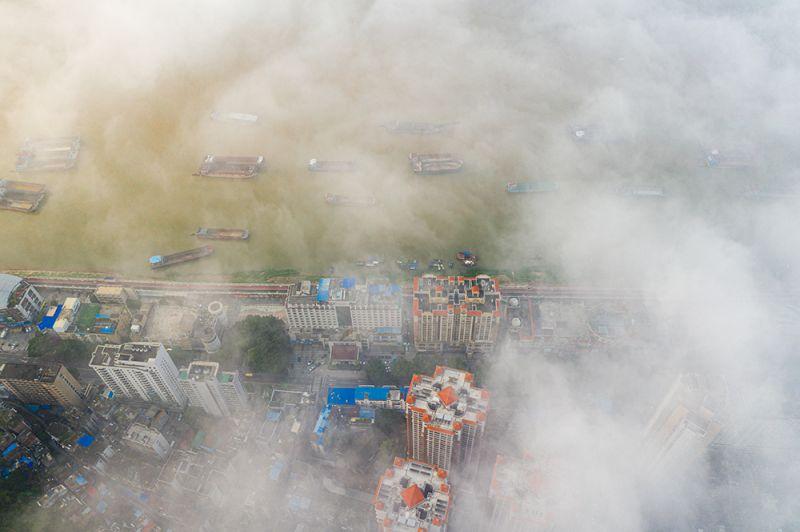4、江河船只和城市建筑在云雾中若隐若现(何华文)