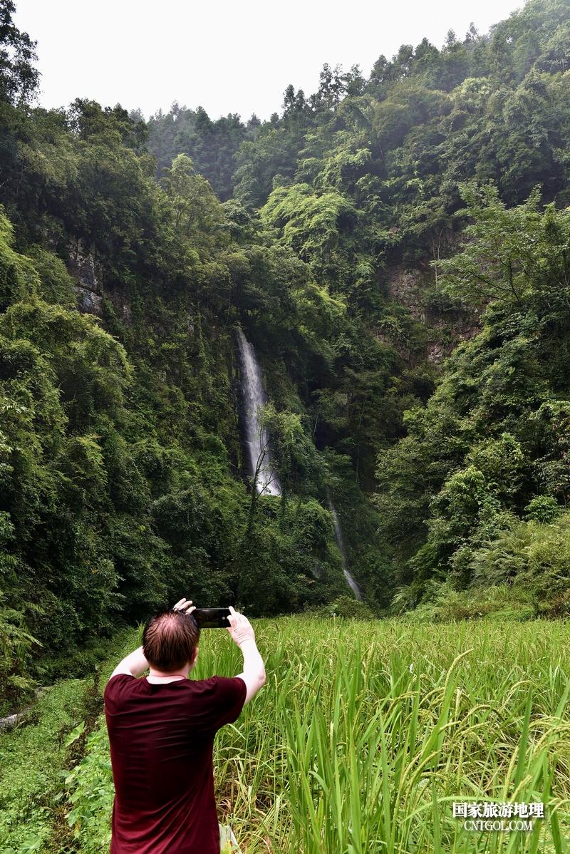 2020年9月10日,游客在贵州省黔东南苗族侗族自治州从江县庆云镇丹阳瀑布拍照。(龙梦前摄)