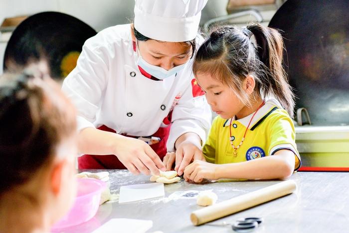 5、2020年11月18日,在广西梧州商贸学校,幼儿园的小朋友与老师一起亲子面点制作体验,从小培养热爱劳动的良好习惯。