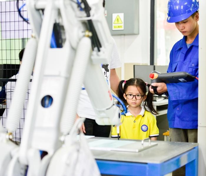 11、2020年11月18日,在广西梧州商贸学校幼儿园的小朋友饶有兴趣参观工业智能制造体验,感受科技的魅力。