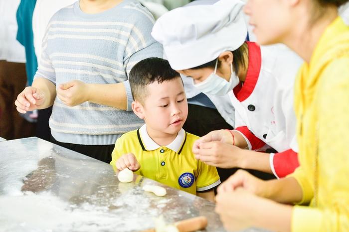 7、2020年11月18日,在广西梧州商贸学校,幼儿园的小朋友与老师一起亲子面点制作体验,从小培养热爱劳动的良好习惯。
