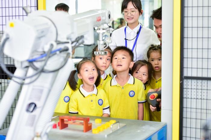15、2020年11月18日,在广西梧州商贸学校幼儿园的小朋友饶有兴趣参观工业智能制造体验,产生好奇,感受科技的魅力。