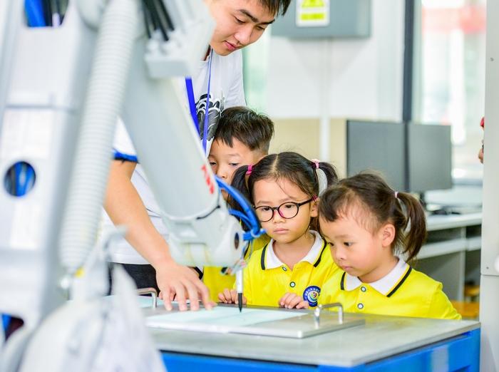 12、2020年11月18日,在广西梧州商贸学校幼儿园的小朋友饶有兴趣参观工业智能制造体验,感受科技的魅力。