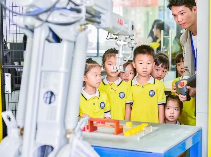 14、2020年11月18日,在广西梧州商贸学校幼儿园的小朋友饶有兴趣参观工业智能制造体验,感受科技的魅力。