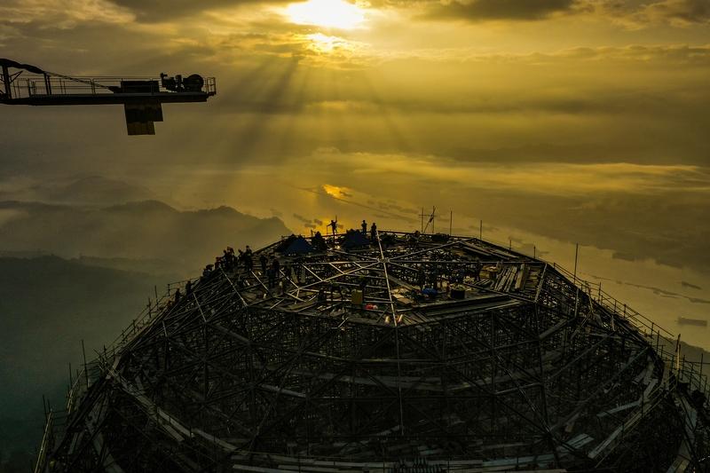 4、每天早上,工人们顺着朝阳爬上塔顶开展新一天的工作。