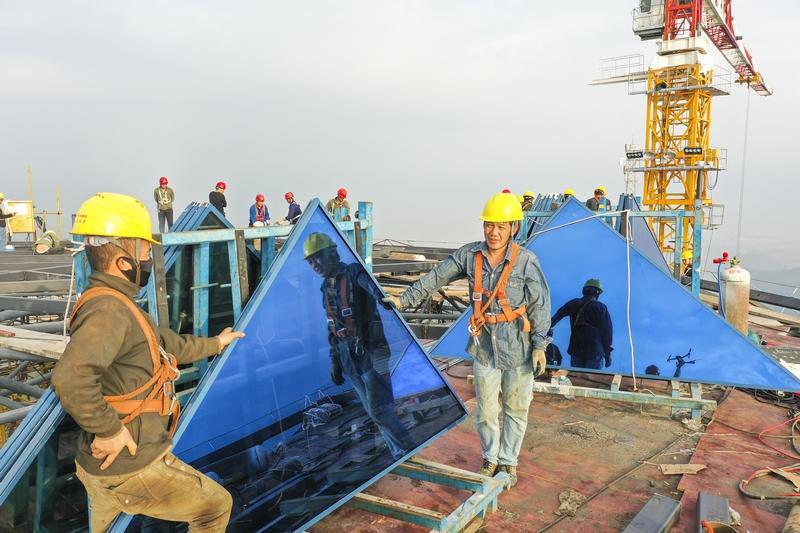 5、工人们爬上塔顶准备工作。