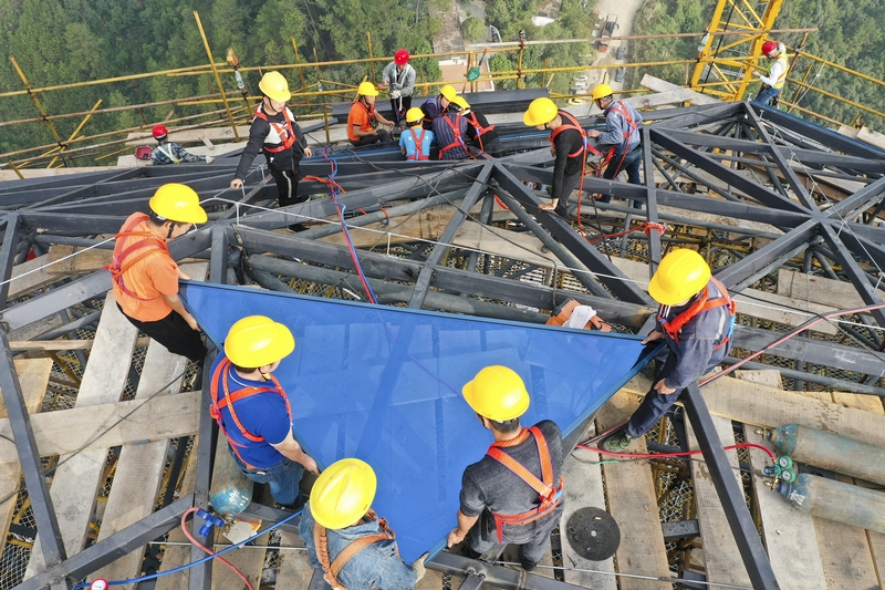 15、工人们上下配合组装幕墙。