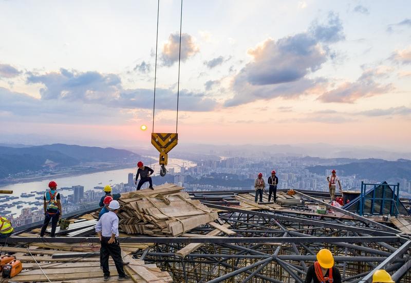 20、夕阳下,工人们忙碌的为西江明珠塔顶玻璃幕墙安装。