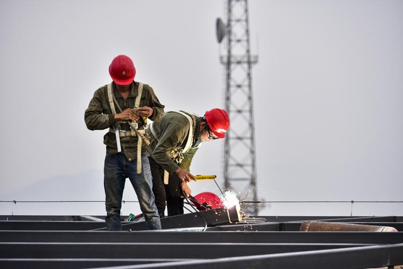 21、工人们在塔顶上焊接幕墙构架。