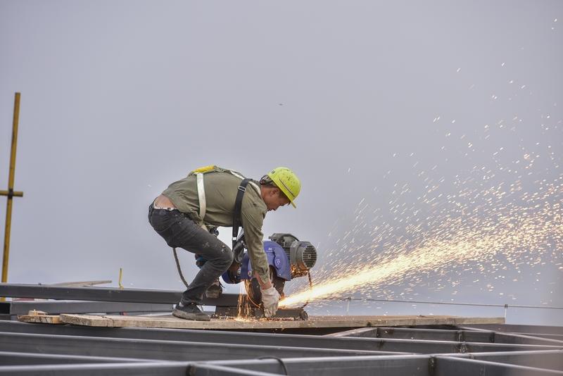 22、工人们在塔顶上切割材料。