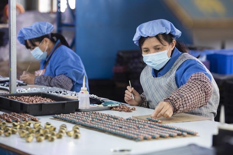 5、金鸡镇民乐村易地扶贫集中安置点的扶贫车间内,200多名工人在玩具加工生产线上忙碌着,对零件进行上色、组装。