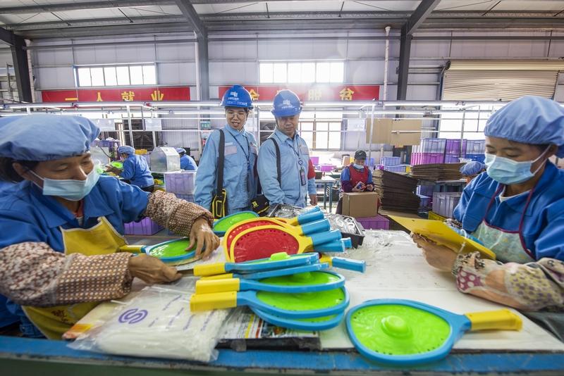 6、金鸡镇民乐村易地扶贫集中安置点的扶贫车间内,200多名工人在玩具加工生产线上忙碌着,对零件进行上色、组装。供电人员上门服务了解企业生产用电需求(何华文)