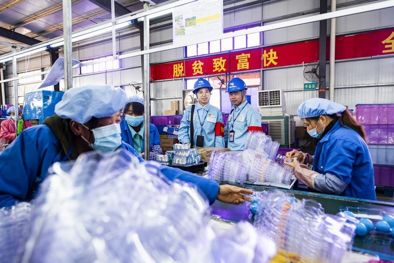 8、金鸡镇民乐村易地扶贫集中安置点的扶贫车间内,200多名工人在玩具加工生产线上忙碌着,对零件进行上色、组装。供电人员上门服务了解企业生产用电需求(何华文)