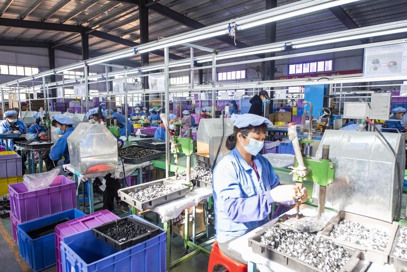 11、金鸡镇民乐村易地扶贫集中安置点的扶贫车间内,200多名工人在玩具加工生产线上忙碌着,对零件进行上色、组装。(何华文)