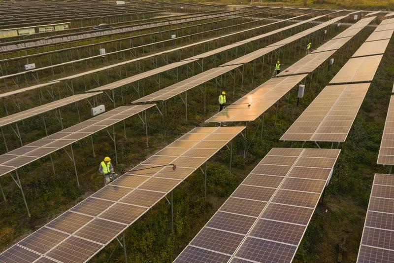 8、2020年12月10日,鸟瞰广西梧州市蒙山县桐油坪工业园区集中式光伏发电项目产业园,整齐的光伏叶片在阳光下闪闪发光,工人们正在清扫叶片。