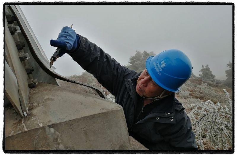2021年第一波寒潮来临,天寒地冻里铁塔钢躯急需巡线人员把脉问诊。图为南方电网云南曲靖供电局输电管理所线路八班对220千伏平花Ⅱ回线22号塔开展覆冰观测。(姜标南)