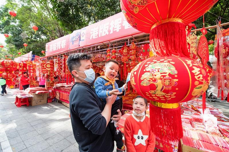 2、2021年2月1日,广西梧州市一位男士带着孩子在梧州市大学路旺城广场年货一条街选购节日饰品。(何华文)