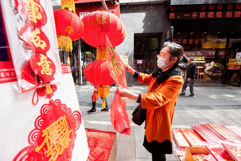 3、2021年2月1日,广西梧州市一位女士在梧州市大学路旺城广场年货一条街选购自己喜欢的节日饰品。(何华文)