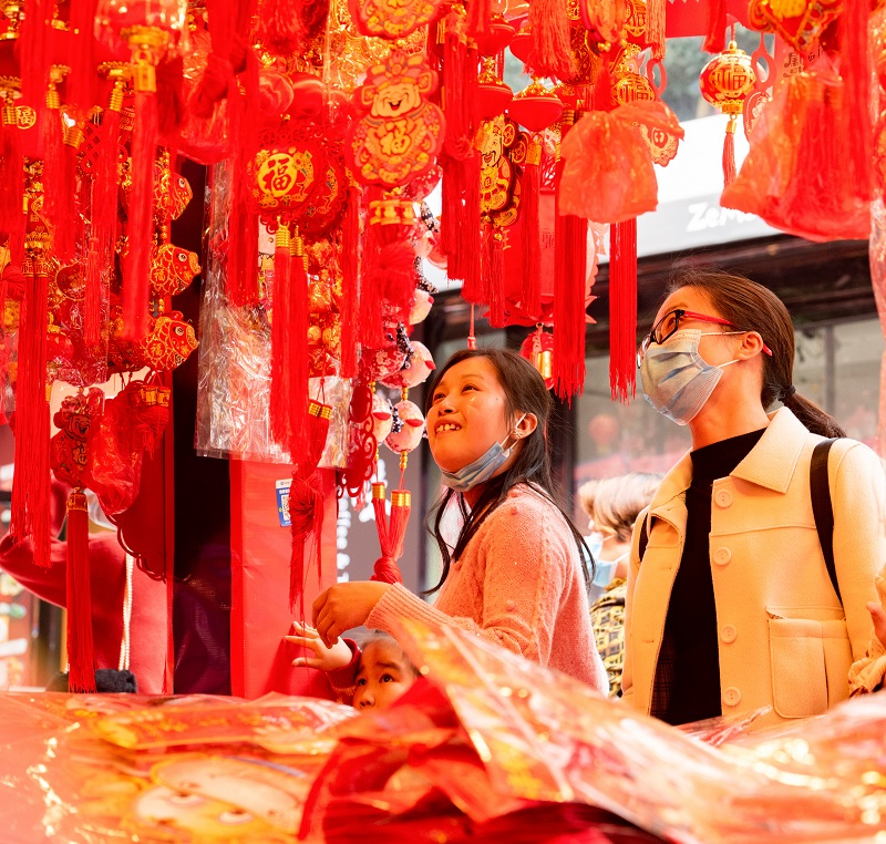 4、2021年2月1日,广西梧州市两位女士带着孩子在梧州市大学路旺城广场年货一条街选购自己喜欢的节日饰品。(何华文)
