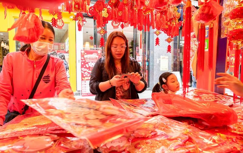 5、2021年2月1日,广西梧州市一位女士在梧州市大学路旺城广场年货一条街选购自己喜欢的节日饰品,利用手机扫码付款。(何华文)
