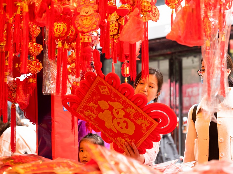 7、2021年2月1日,广西梧州市两位女士在梧州市大学路旺城广场年货一条街选购自己喜欢的节日饰品。(何华文)