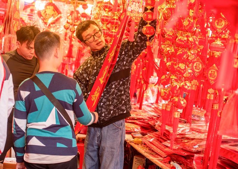 14、2021年2月1日,在广西梧州市大学路旺城广场年货一条街市民在选购自己喜欢的对联。(何华文)