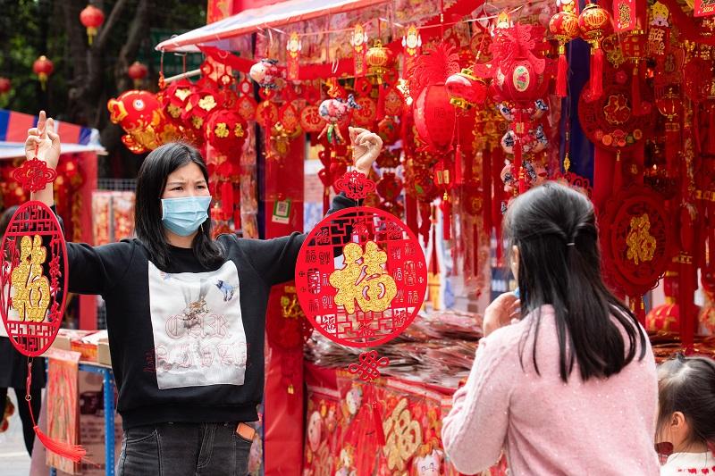 16、2021年2月1日,广西梧州市大学路旺城广场年货一条街商家向顾客展示自己的商品。(何华文)