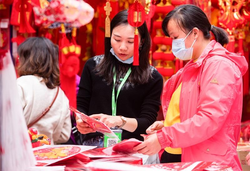 18、2021年2月1日,在广西梧州市大学路旺城广场年货一条街商家向顾客介绍节日饰品。(何华文)