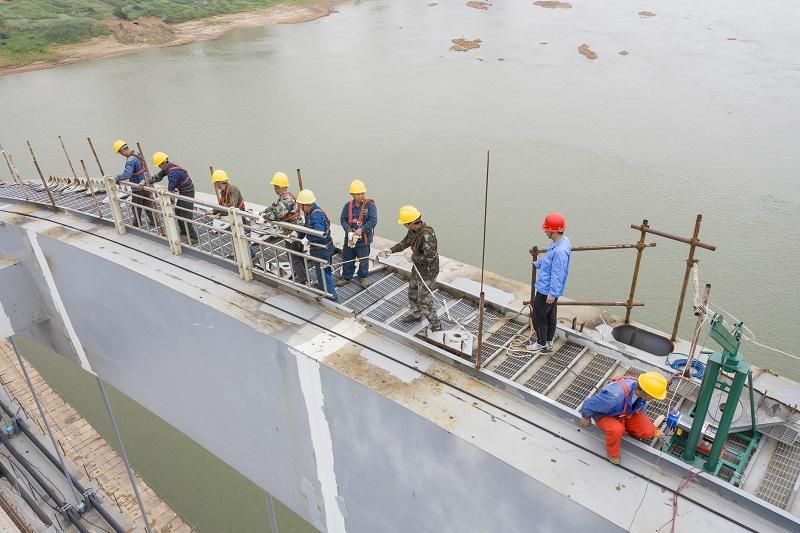 8、2021年4月4日,位于广西壮族自治区梧州市西江四桥施工现场,工人们加班加点在各自岗位上忙碌着拆除塔架、桥面钢筋焊接、安装护栏、清理等,一派繁忙的施工景象。