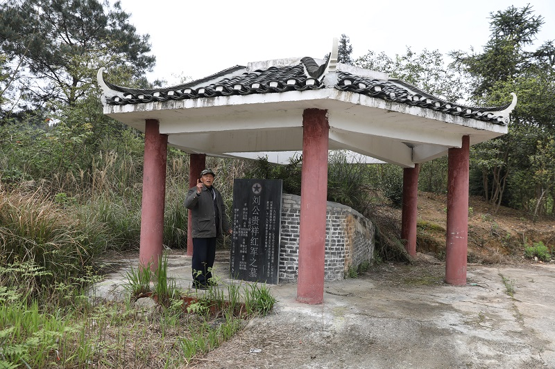 图为黎平县洪州镇草坪村老党员杨家光在老红军刘贵祥墓前讲述红军故事  那志奎摄