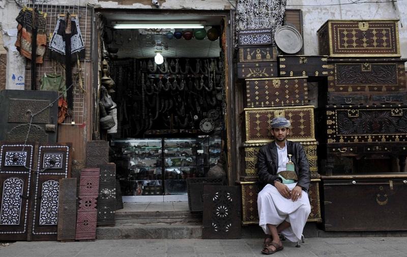 也门首都萨那古城的店铺外等待顾客的商贩