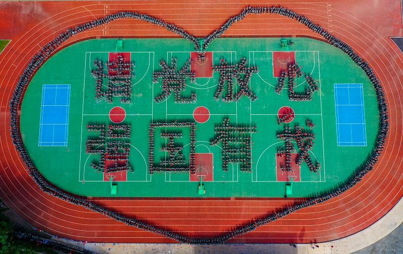 """2021年9月1日,广西梧州商贸学校2000多名新生在操场上摆成""""请党放心,强国有我""""字样和心型图案,以奋进姿态开启新学年新征程。"""