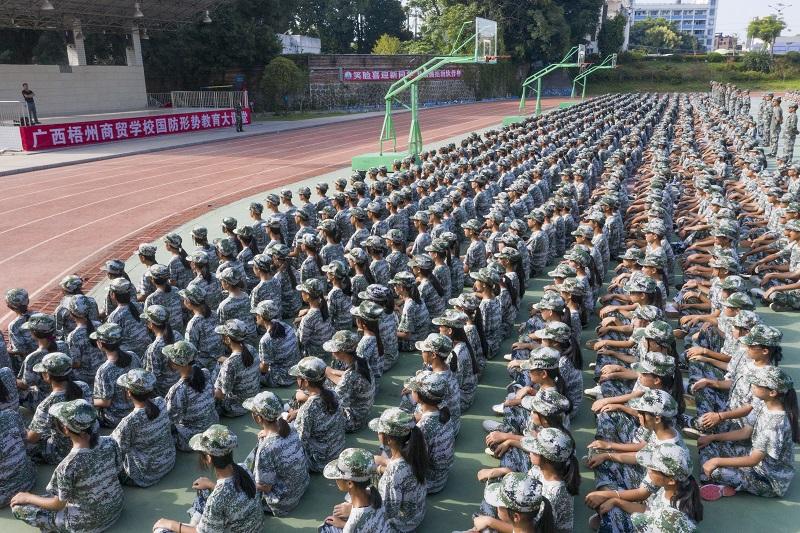 2021年9月1日,广西梧州商贸学校新生在操场上认真聆听国防形势教育课。