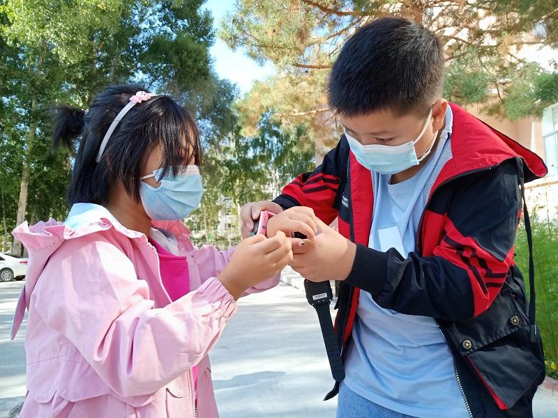 来自阿勒泰市阿苇滩寄宿制学校5年级的学生伊米热尼·买买提正在给妹妹戴4G儿童智能手表