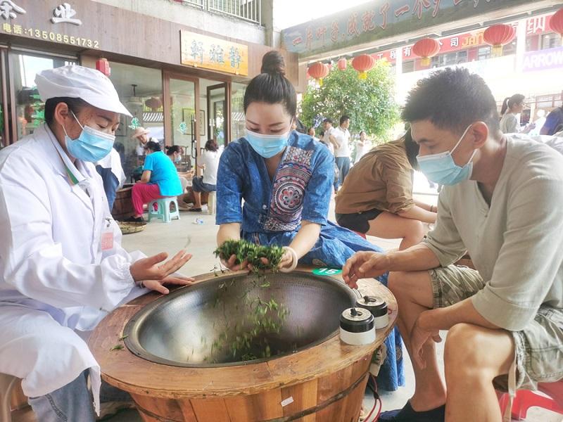 游客李女士在体验手工炒茶(石光照摄)