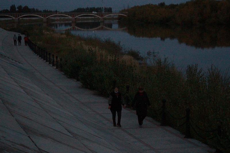 游客在流经布尔津县境内的额尔齐斯河畔散步